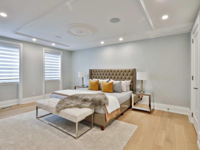 custom bedroom with wooden floor and baseboard trim