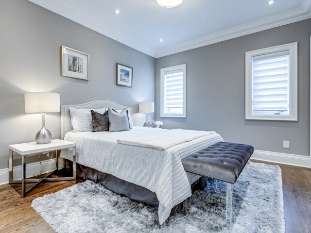 amazing bedroom with gray wall painting and baseboard trim - custom home experts