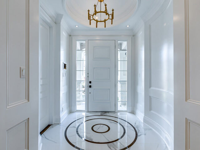luxury hallway with custom interior doors and coffered wall decor