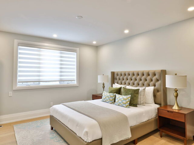 modern bedroom with wooden floor and potlights - custom home experts