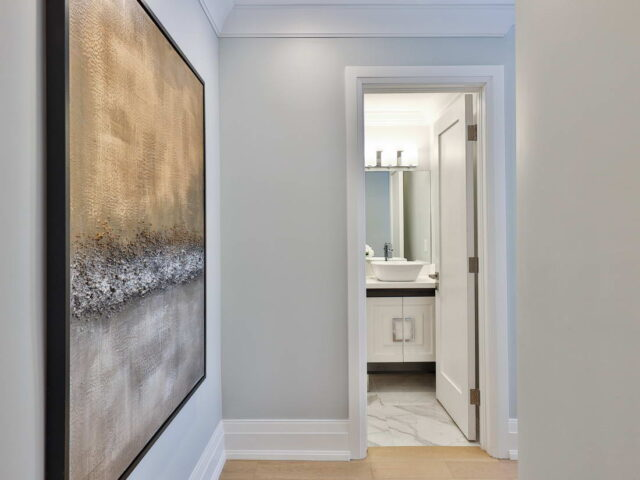 custom hallway with crown moulding and baseboard trim