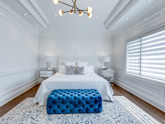 custom bedroom with coffered wall decor and baseboard trim - custom homes