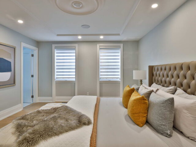 amazing bedroom with gray wall paint and baseboard trim - custom home experts