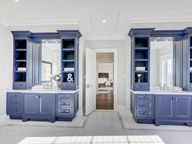 custom bathroom with blue vanity and crown moulding - custom homes