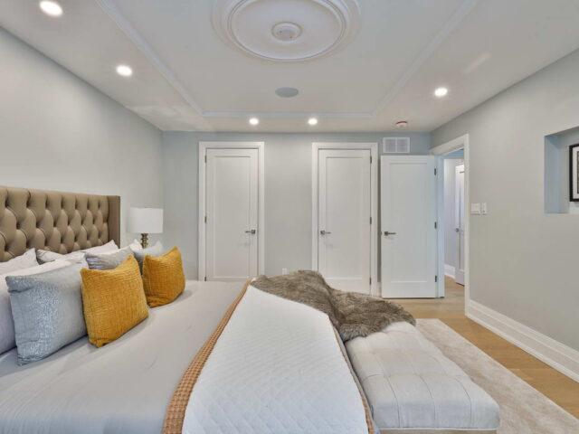 custom bedroom with wooden floor and carpet - custom home contractor