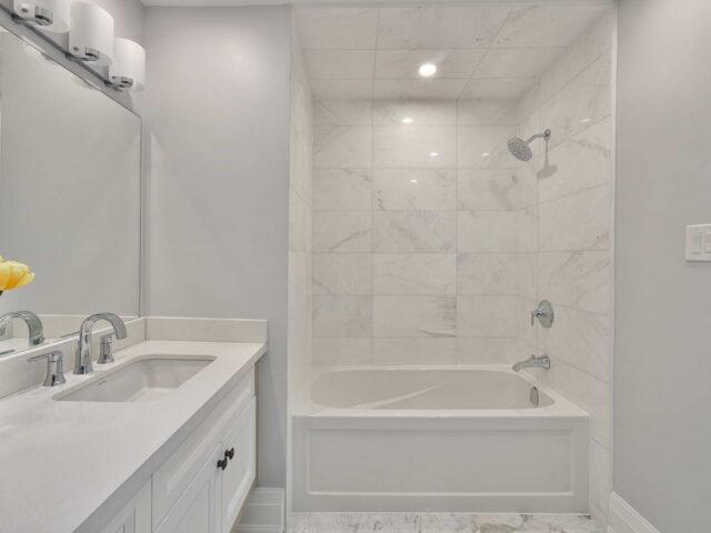 modern bathroom with bathtub and white vanity - custom home contractor